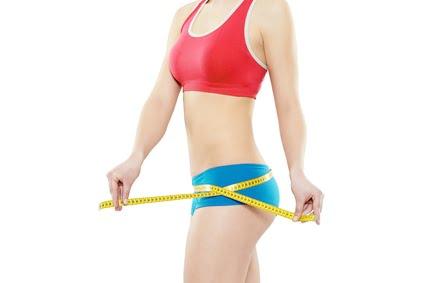 donna che si misura i fianchi con metro perché deve ritrovare la forma per la prova costume