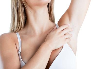donna che si tocca ascella prima di mettersi un deodorante roll-on da viaggio