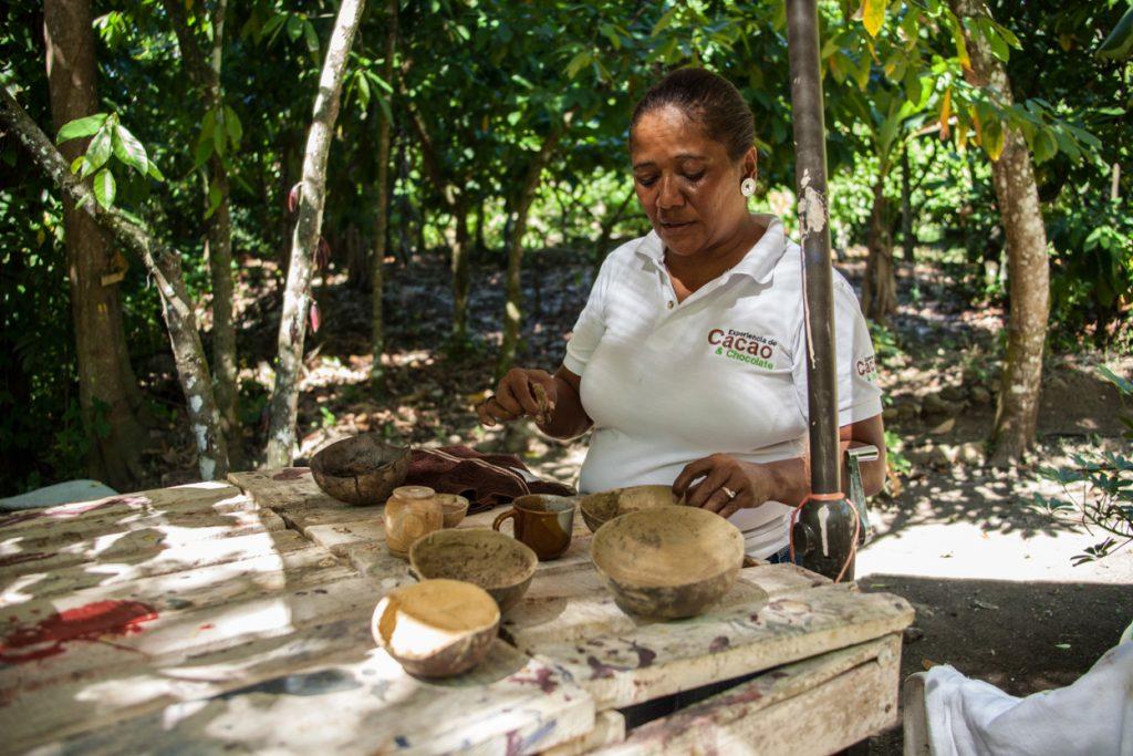donna che fa vedere cacao durante una escursione nel cioccolato