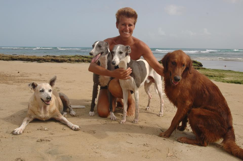 una donna sulla spiaggia con i suoi cani che ha deciso di vivere in repubblica dominicana