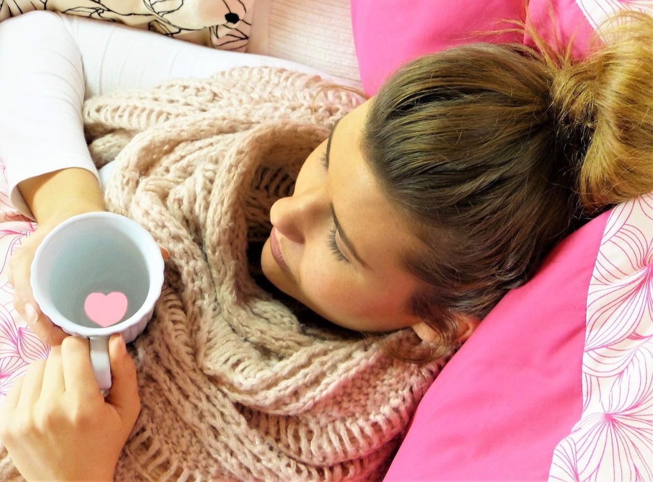 donna a letto che beve tisana per prevenire l'influenza in modo naturale