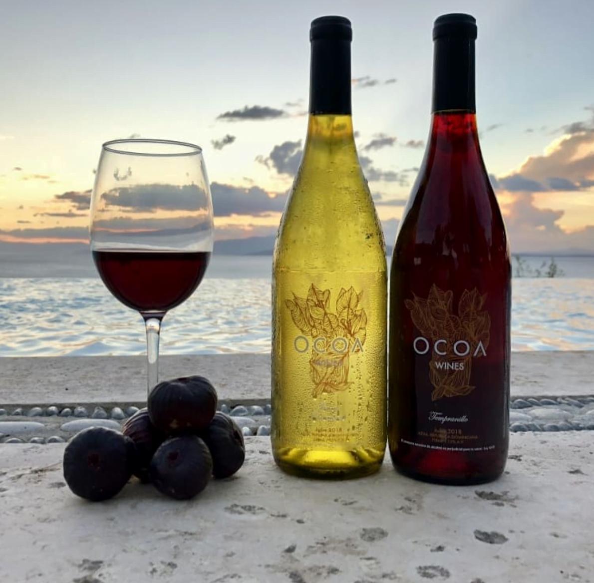 due bottiglie di vino con bicchiere del primo vigneto dei caraibi
